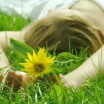 Kvinna ligger i grönt gräs med vit klänning och gul blomma