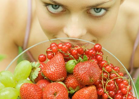 Kvinna med massa frukt och bär