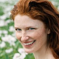 Lycklig kvinna med rött, tjockt hår