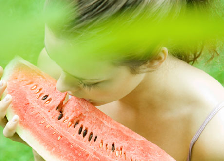 Tjej som äter vattenmelon stående