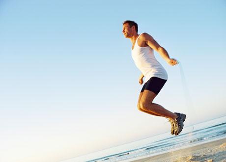 Man som hoppar hopprep på strand