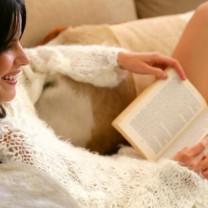 Glad kvinna som läser bok
