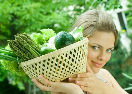 Kvinna som håller i en korg med grönsaker