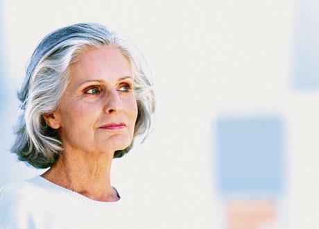 Kvinna i vit tröja och grått hår
