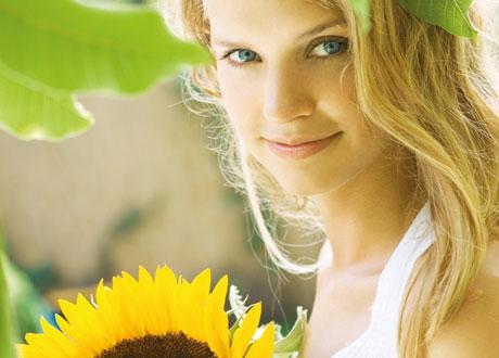 Glad tjej med blad och solros