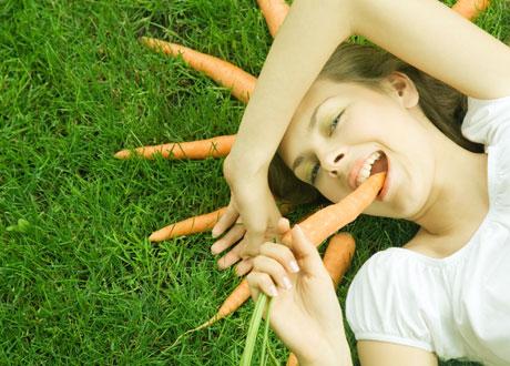 Kvinna som ligger i gräset och äter morötter