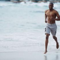 Man som springer på stranden