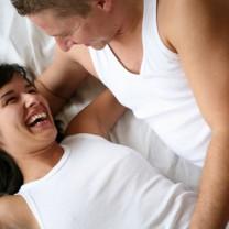 Skrattande par i sängen