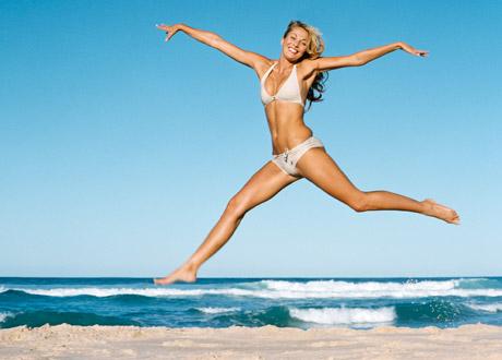 Glad tjej som hoppar på stranden