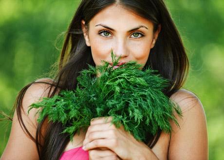 Kvinna i brunt hår som äter grönt