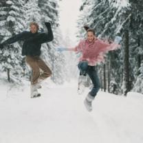 Ett glatt par som hoppar i snön