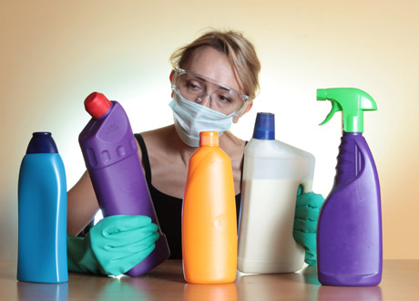 Kvinna med munskydd och rengöringsflaskor