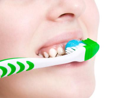 Kivnna som borstar tänder