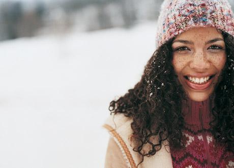Vacker kvinna med fräknar i snön