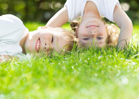 Två glada barn i gräset