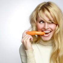 Glad tjej som äter en morot