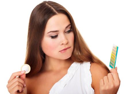 Kvinna som försöker välja mellan kondom och p-piller