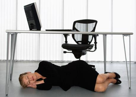Kvinna som sover under skrivbordet