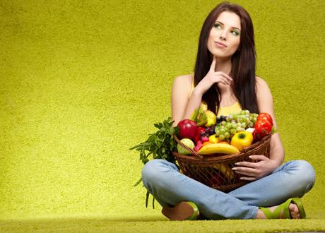 Kvinna med fruktkorg i famnen