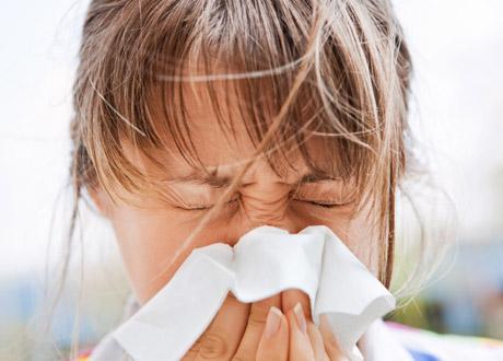 Ung kvinna som nyser i näsduk