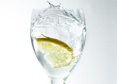 Ett högt glas på fot med citronskiva och vatten som splashar.