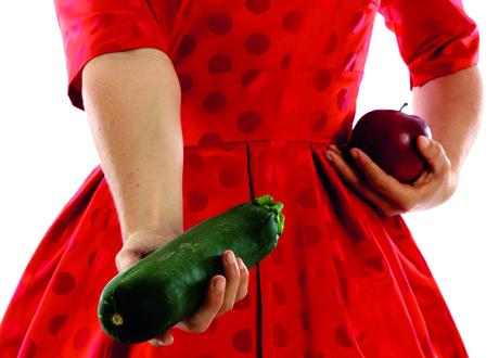 Man ser livet på kvinna i röd klänning som håller en zucchini och ett äpple