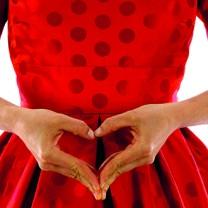 Kvinna som formar hjärta med händerna framför magen