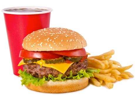 frilagd bild på röd pappmugg med mörk läsk, en hamburgare och pommes