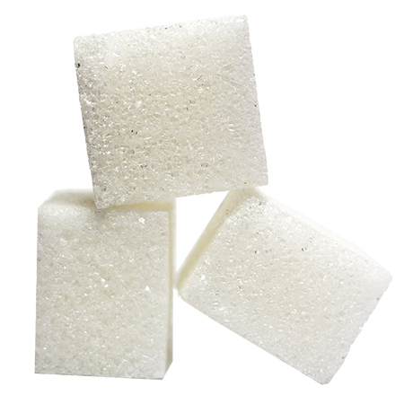 Närbild på tre sockerbitar mot vit bakgrund
