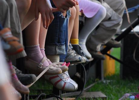 Barn sitter stilla på bänk, endast benen syns