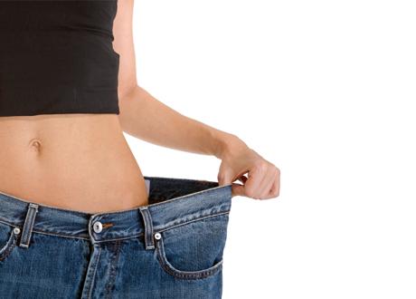 Smal kvinna i ett par för stora jeans. Bara kroppen syns