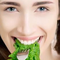 Mörkhårig ung kvinna äter spenatblad