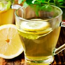 Två koppar te med citron gröna blad i bakgrunden på träbord