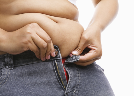 Kvinna försöker få ihop dragkedjan på sina jeans, inget huvud syns