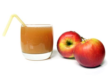 Glas med äppeljuice bredvid två äpplen röda