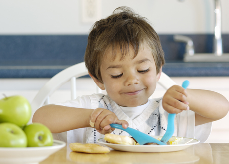 Treårig mörkhårig pojke äter med kniv och gaffel