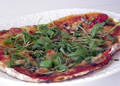 En pizza med tomatsås, ost och ruccola som topping