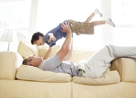 Pappa leker med sin son ligger på soffan slänger upp sonen i luften