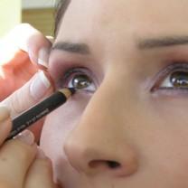 Kvinna blir sminkad med kajal runt ögonen