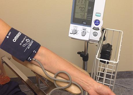 En person gör blodtrycksmätning med maskin, endast armen och maskinen syns