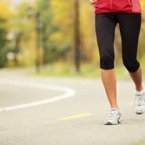 En löparkvinnas ben i svarta leggings och vita skor på asfalt med skog i bakgrund