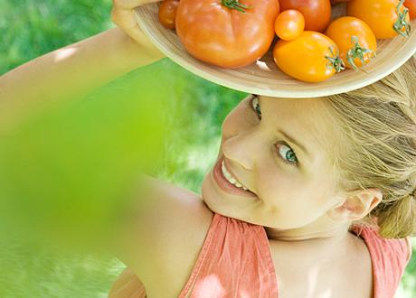 Leende kvinna med ett fat tomater på sitt huvud