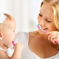 Mamma och flickbebis borstar tänderna