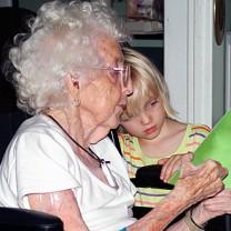 Äldre vithårig kvinna läser med sitt barnbarn