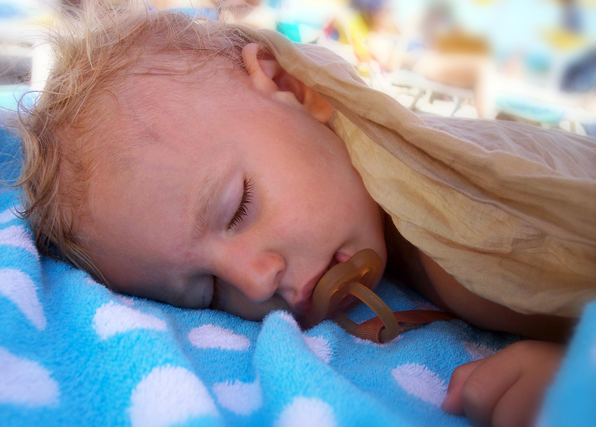 En tvååring sover på filt utomhus med naturgumminapp i munnen