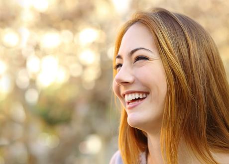 Lyckligt leende tjej med rött hår