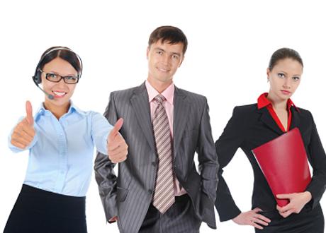 Två kvinnor och en man i kostymer står upp