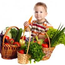 Liten pojke sitter bredvid korg med grönsaker har morot i handen