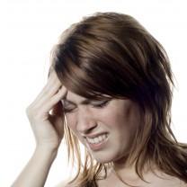 Ung tjej håller handen på pannan ser ut att ha huvudvärk