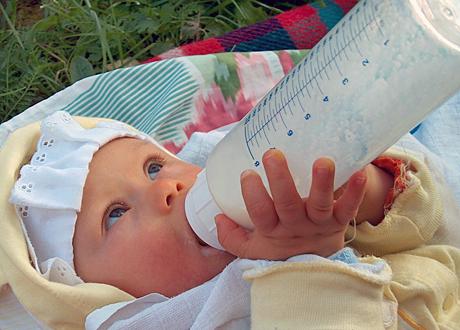 Bebis håller i och suger på nappflaska